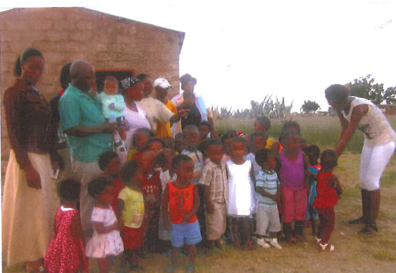 Volunteers and church committee members with some of the children in front of an outstation church that provides shelter to the children.